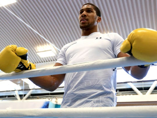 Britain's World Heavyweight Champion Anthony Joshua holds the top rope during the workout at the English Institute of Sport, Sheffield England Wednesday March 21, 2018. Joshua with fight New Zealand's Joseph Parker in a world title fight in Cardiff on March 31, 2018.  (Mike Egerton/PA via AP)