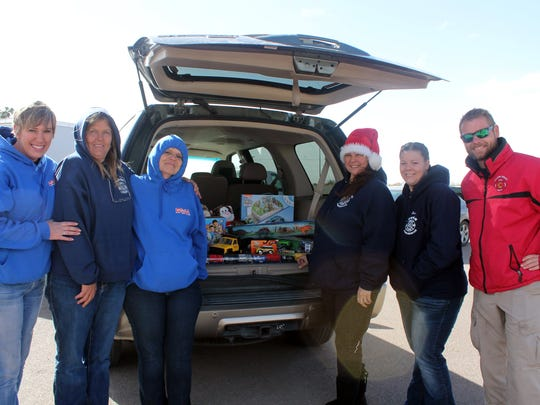 Stephanie Hale, Jackie Moretz, Vickie Compton, Nina Fierro, Heather Bowlby and Steffen Milner, all from various volunteer fire departments, worked to collect presents Saturday.