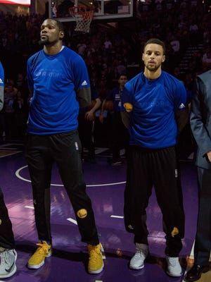 Golden State Warriors forward Kevin Durant and guard Stephen Curry during the national anthem before the game against the Sacramento Kings.