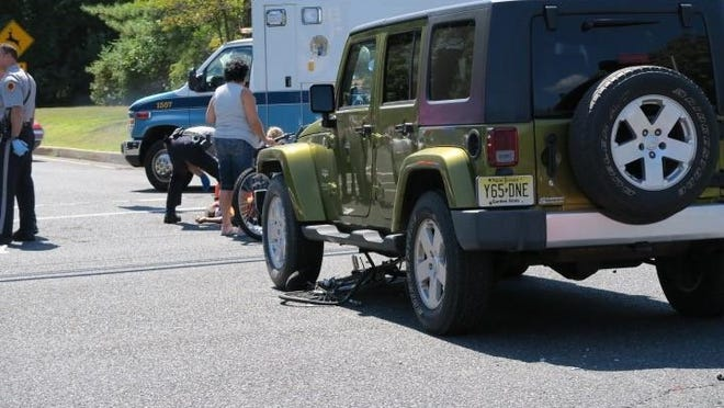 A bicycle lies under the wheel of a green sport-utility vehicle after a Sunday crash on Kozloski Road.