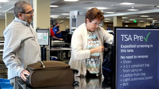 Two travelers slide their luggage through the TSA PreCheck security screening at the Reno-Tahoe International Airport last year.