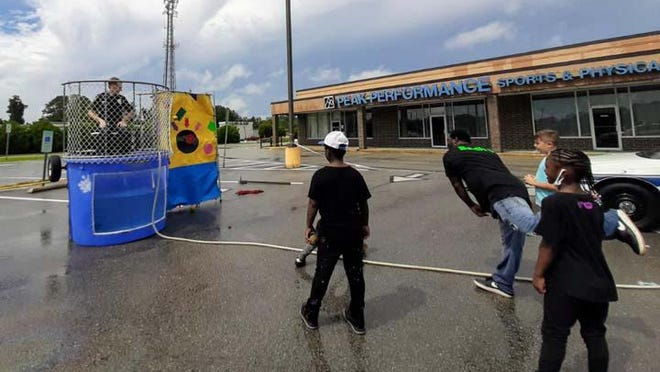 Back to School Bash 5 was recently held at Look at Me Now Cutz, 1146 Gum Branch Road, Jacksonville. JPD and Dare came out and volunteered to be in the dunking booth. Students received free book bags, school supplies with food and live entertainment for the community.
