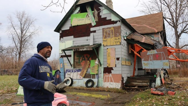 "Artist Tyree Guyton works outside the ""Taxi House"" which became the 12th of the Heidelberg Project structures to burn Sunday November 23, 2014 in Detroit."