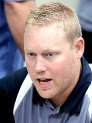 Northeastern football coach Jon Scepanski talks with