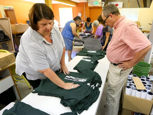 Stephanie Patterson, events coordinator for the Salem Art Association, left, and Don Hudgins, director of special events, sort t-shirts during a Salem Art Fair committee meeting at the Bush Barn Art Center. The two oversee the execution of the art fair.