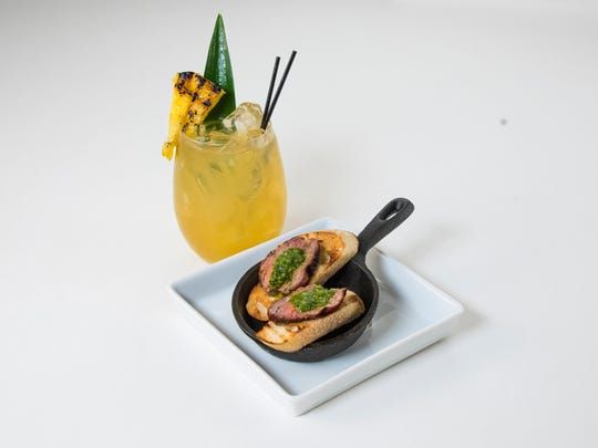 A Smoky Piña cocktail includes mezcal, made from roasted piña, the heart of the agave plant. Wood-fire crostini add to the smokiness.