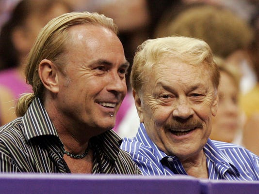 FILE - In this Aug. 23, 2005, file photo, Los Angeles Sparks owner Jerry Buss, right, who has since died, and son Johnny watch the team play the Minnesota Lynx during the second half at Staples Center in Los Angeles. Jeanie Buss went to court to stop what her attorneys call an attempt by her brothers Jim and Johnny Buss to oust her as controlling owner and president of the Los Angeles Lakers. The matter was dropped Friday, March 3, 2017, when Jeanie Buss withdrew her request for a temporary restraining order to stop the brothers from moves against her, but it may just be the opening skirmish in a bigger family fight over one of the most storied franchises in sports. (AP Photo/Chris Carlson, File)