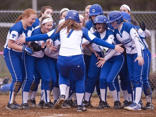 The Missisquoi Thunderbirds celebrate with Sarah Harvey (7) at home plate after her home run against Essex during Thursday's high school softball game in Essex.
