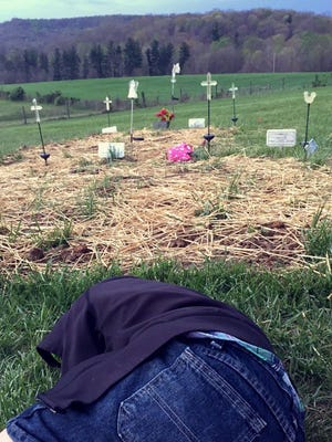 "Brentley Rhoden, now 4, lies next to the graves of his father, aunt, uncle and grandparents on Easter, April 16, 2017, in rural Pike County, Ohio. He was asleep in his dad's home when Clarence ""Frankie"" Rhoden and girlfriend Hannah Gilley were killed."