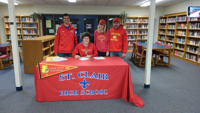Surrounded by his parents and his high school basketball coach, St. Clair senior Ben Davidson signed his national letter-of-intent.