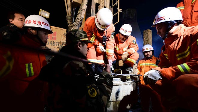 In this Dec. 28, 2015 photo provided by China's Xinhua News Agency, rescuers try to contact the trapped people at a collapsed mine.