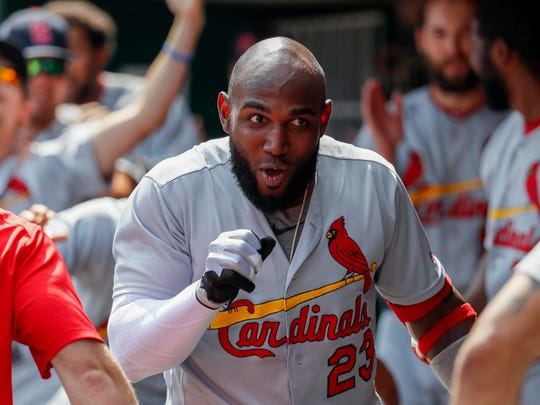 St. Louis Cardinals' Marcell Ozuna celebrates in the dugout after hitting a solo home run off Cincinnati Reds starting pitcher Luis Castillo in the first inning of a baseball game, Saturday, June 9, 2018, in Cincinnati. (AP Photo/John Minchillo)