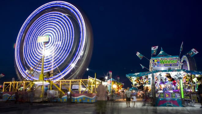 A ferris wheel at the Delaware State Fair glows through a long-exposure photograph on Friday night, July 24, 2015.