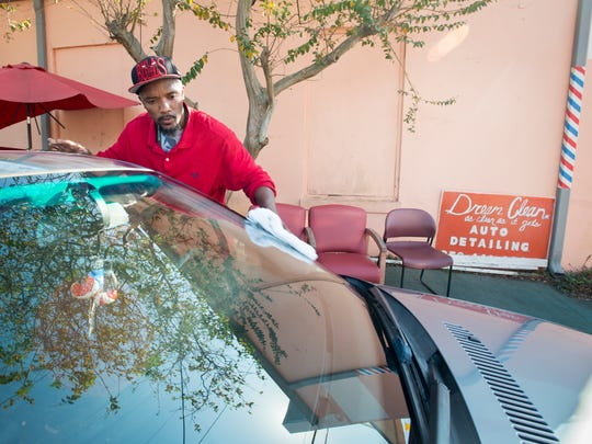 Dream, Dream Clean, wipes down a car at his detailing business outside of The Network Beauty & Barbershop in Brownsville on Thursday, November 16, 2017.  The Network owner Floyd Jones says that his customers can save time by getting their car cleaned while they are inside getting their hair styled.