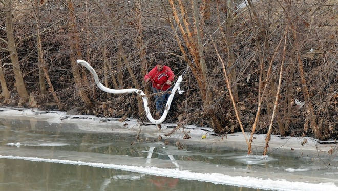 A Freedom Industries worker places a boom in the Elk River on Thursday.