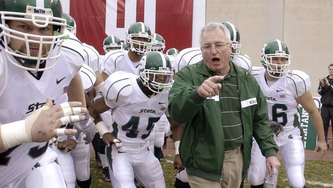 Michigan State interim coach Morris Watts, second from right, leads the Spartan's onto the field to face the Indiana Hoosiers in Bloomington, Ind., Saturday, Nov. 9 2002.