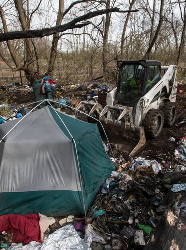One of several tents that made up a homeless camp in Butchertown is removed by Metro Sanitation workers. March 9, 2018.