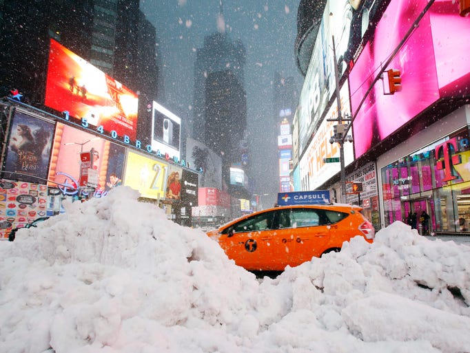 A taxi drives past piles of snow as a storm sweeps