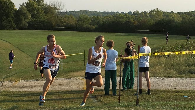 Hayden junior Tanner Newkirk, right, battles Manhattan senior Daniel Harkin as the duo climbs the final hill in last Saturday's Washburn Rural Sunflower Showdown at T-Town. Newkirk, the City Athlete of the Week, won the race in a five-kilometer time of 15:40.7.