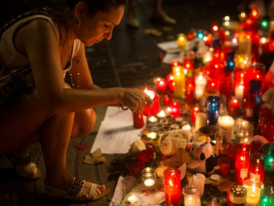 A woman lights a candle at a memorial for victims of the vehicle attacks on Barcelona's historic Las Ramblas promenade in August.