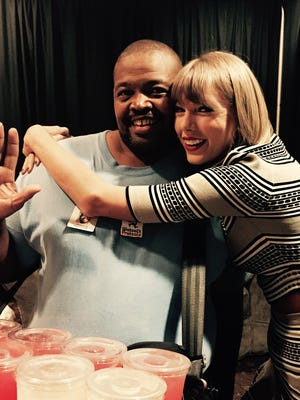 Derrick Moore gets a hug from pop star Taylor Swift at Gila River Arena.