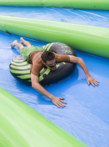 People brave the 1000-foot slide that goes down Palisades Blvd. on their tubes during Slide the City, Saturday, April 25, 2015, in Fountain Hills, Ariz.