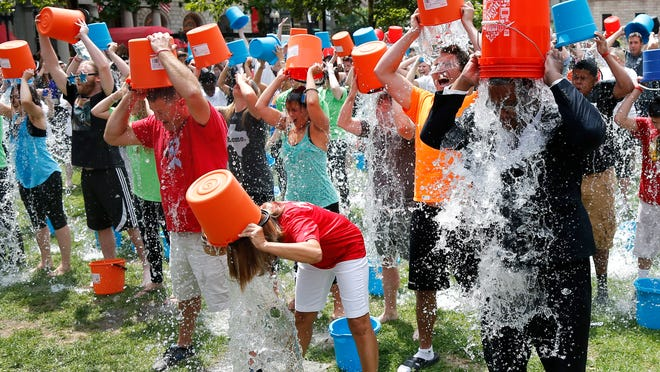 Boston City Councillor Tito Jackson, right, leads about 200 people in the ice bucket challenge at Boston's Copley Square on Aug. 7, 2014 to raise funds and awareness for ALS.