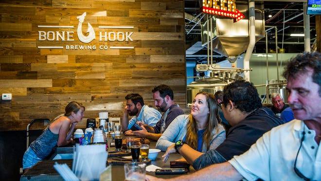 People sit along the bar with their beers at Bone Hook Brewing Co. in North Naples on Friday, June 16, 2017.