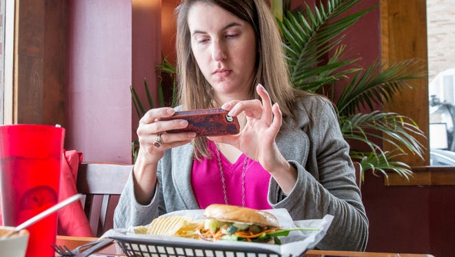 Kelsey Jones, a local food blogger, takes some photos of her food at Two Johnny's Tuesday afternoon in downtown Muncie for her blog. Jones aims to deliver a better understanding of the local food culture through her own dining experiences.