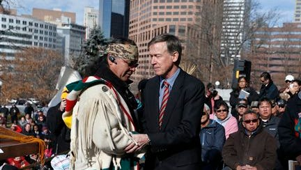Gov. John Hickenlooper, center right, greets Northern Cheyenne tribal leader Otto Braidedhair, after speaking to members and supporters of the Arapaho and Cheyenne Native American tribes at a gathering marking the 150th anniversary of the Sand Creek Massacre, on the steps of the state Capitol in Denver, today. During his speech, Hickenlooper apologized on behalf of the state for the massacre.