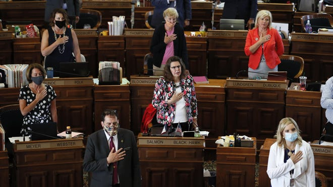 In this Wednesday, June 3, 2020 file photo, State Representatives stand at their desks during the Pledge of Allegiance in the Iowa House chambers, at the Statehouse in Des Moines, Iowa. Republican governors and state lawmakers in many states have followed President Donald Trump's lead in downplaying the seriousness of the coronavirus virus, refusing to wear masks and fighting against coronavirus restrictions on businesses and social gatherings. Revelations that the president and first lady are now among those who have tested positive for the disease did little to change their thinking.