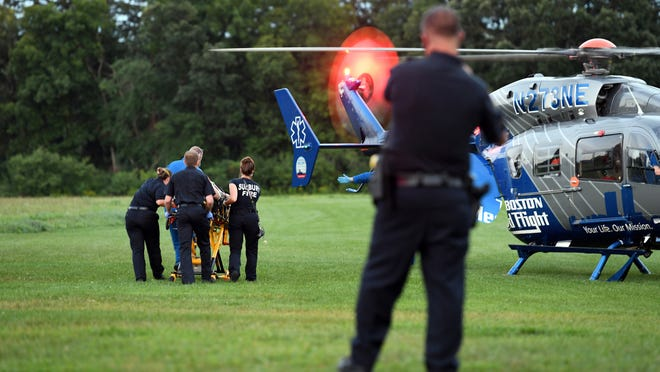 Sudbury Fire Department paramedics and Boston MedFlight staff take a man to a helicopter at Davis Field on Monday evening after the man suffered injuries in a pool accident on North Road in Sudbury.