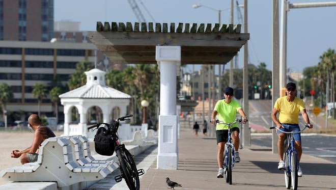 GABE HERNANDEZ/CALLER-TIMES People ride their bikes along the seawall, which is part of the bayfront park, in August.