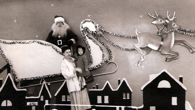 Charlene Dickinson holds her daughter Paula Dickinson, 2, as they pose with Santa at Park Center at Park and Getwell during a shopping trip on Dec. 17, 1955.