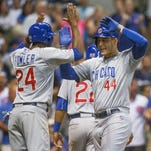 Chicago Cubs' Anthony Rizzo gets a high five from teammate Dexter Fowler after hitting a three run home run off Milwaukee Brewers' Jeremy Jeffress during the eighth Thursday in Milwaukee.