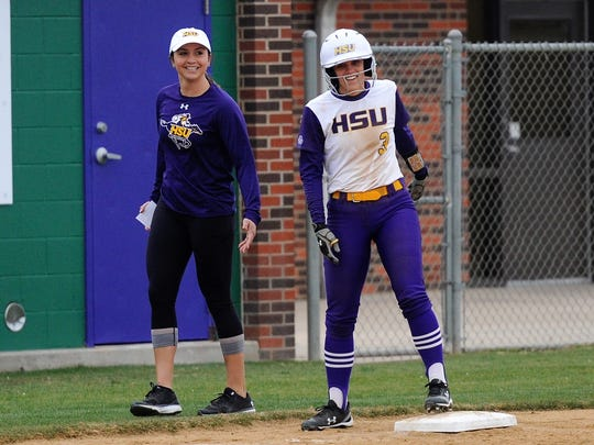 Hardin-Simmons coach Chanin Naudin laughs with Kirsten Kenyon (3) after she reached third base on a bunt and an error in the Cowgirls' 7-6 loss to McMurry on Tuesday, Feb. 13, 2018.