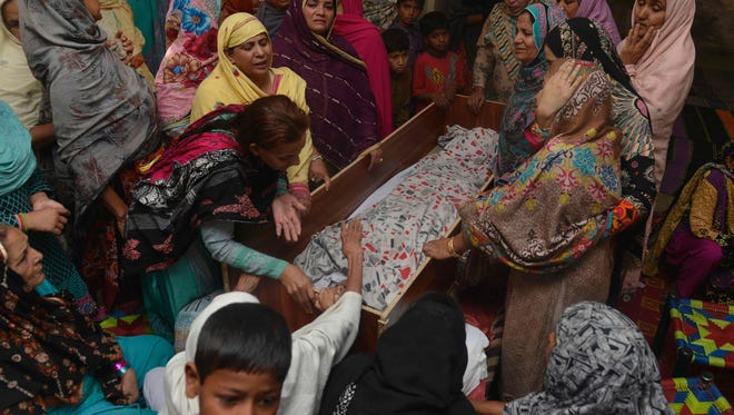 Pakistani relatives mourn over the body of a victim during a funeral following an overnight suicide bombing in Lahore on March 28, 2016.