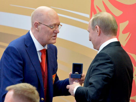 FILE - In this Friday, April 22, 2016 file photo Russian two time Olympic champion Vladimir Petrov, left, gives Russian President Vladimir Putin a champion's ring for CSKA's victory at the Russian ice hockey championship during a meeting on sports issues in Kazan, 720 kilometers (450 miles) east of Moscow, Russia. Vladimir Petrov, a two-time Olympic hockey champion who was on the Soviet Union team that lost to the United States at the 1980 Lake Placid Games, died Tuesday. He was 69. (Alexei Druzhinin/Pool Photo via AP, File)