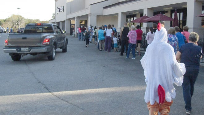 A long line of local residents await the opening of Fairview's new Dirt Cheap store.