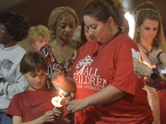 Christine Rials, right, lights the candle of her son, Isaiah, during a candlelight vigil Monday, Feb. 19, 2018, at East Brent Baptist Church in Pensacola to honor the victims of the school shooting last week in Parkland.