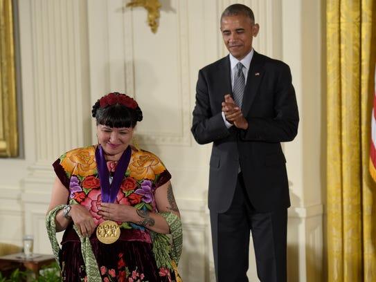 President Barack Obama applauds author Sandra Cisneros