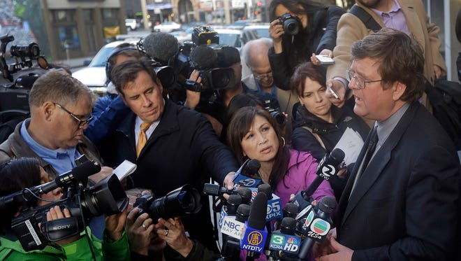 Attorney Paul DeMeester, right, who is representing Sen. Lelan.d Yee, D-San Francisco, speaks with reporters outside the San Francisco Federal building Wednesday.
