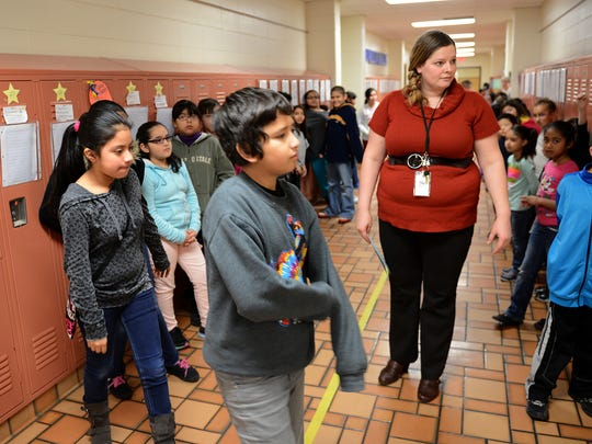 Fourth-grade bilingual teacher Ann Klapatch greets students Thursday in the hallway at Nicolet Elementary School.