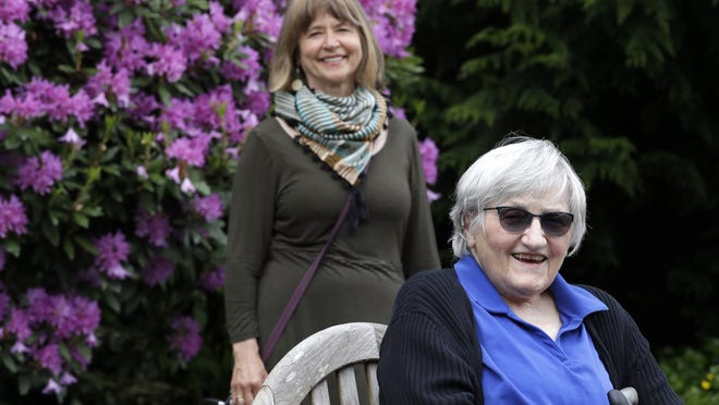 Jessie Cornwell, a resident of the Ida Culver House Ravenna, right, poses for a photo with the Rev. Jane Pauw, in Seattle on May 21. Cornwell tested positive for the coronavirus but never became ill, and may have been infectious when she shared a ride to Bible study with Pauw, who later got sick with COVID-19.   [Elaine Thompson/Associated Press)
