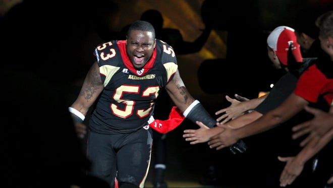 Iowa Barnstormers' #53 Mike Lewis slapped hands with fans during player introductions before arena football game against the San Antonio Talons at Wells Fargo Arena on Saturday night  June 29th, 2013.