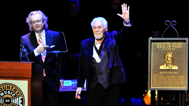 Kenny Rogers, right, waves during the Medallion Ceremony at Country Music Hall of Fame in Nashville on Sunday, Oct. 27, 2013.