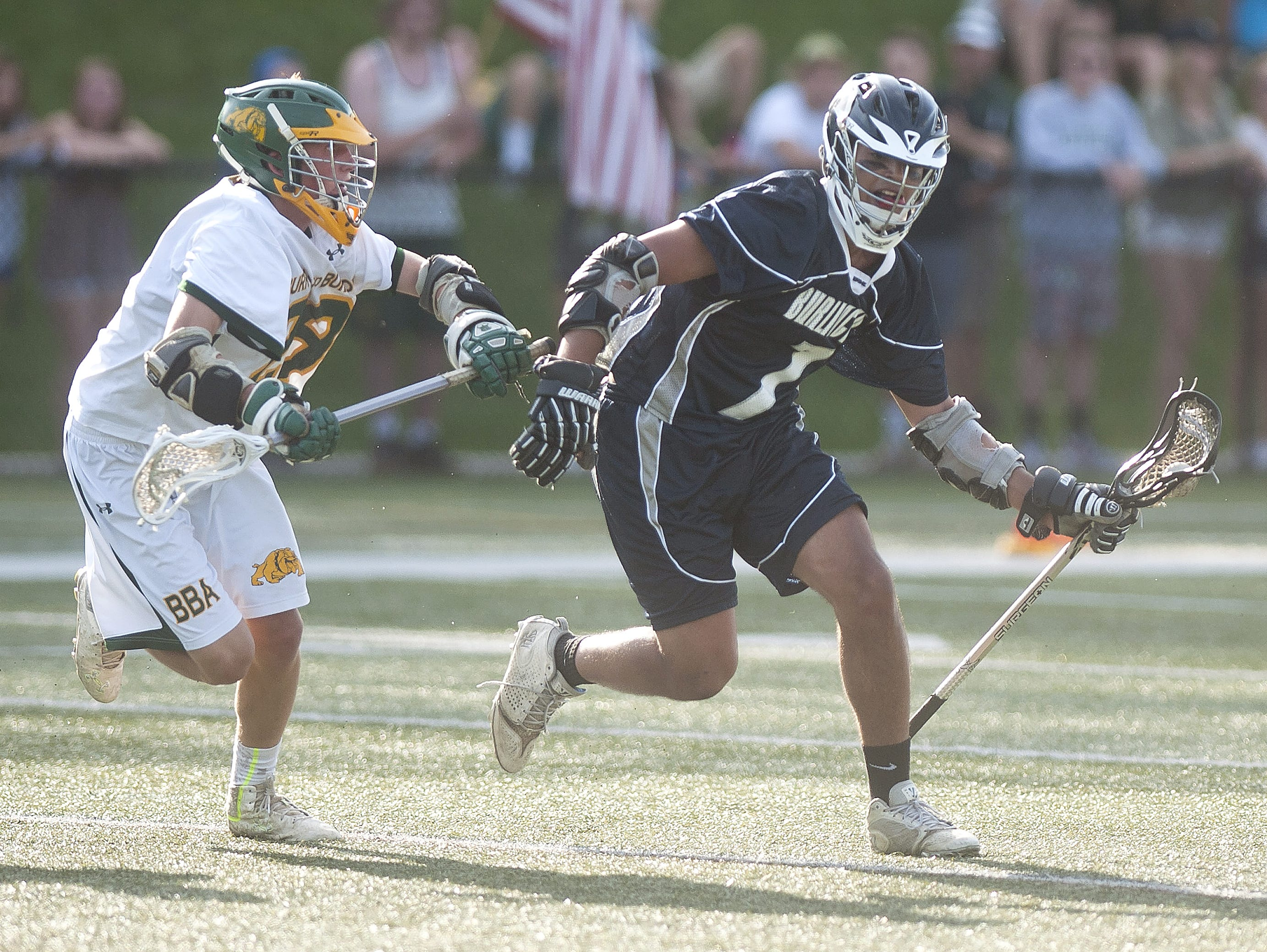Burlington's Sevin Gulfield, right, controls the ball against a Burr and Burton defender during the Division II boys lacrosse championship game on Thursday at Castleton State College.