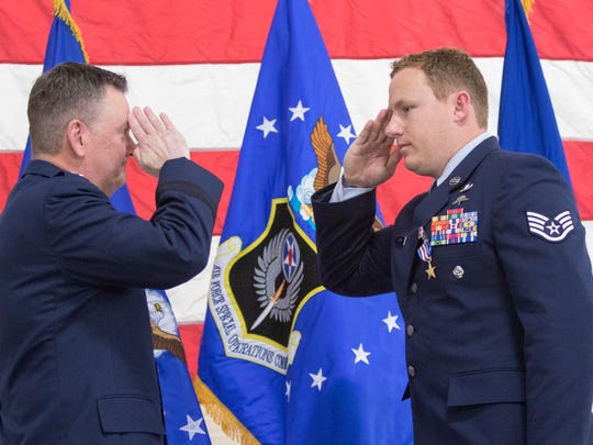Lt. Gen. Brad Webb, left, salutes Staff Sgt. Christopher Lewis after presenting him with The Silver Star for Gallantry in Action on October 20, 2016 during a ceremony at Hurlburt Field in Florida on Friday, January 19, 2018.