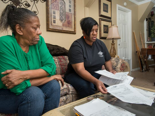 Sisters Patricia Robbins, left, and Beverly Gulley sort through documents concerning their childhood home on Louis Street in Cantonment on Wednesday, February 21, 2018.