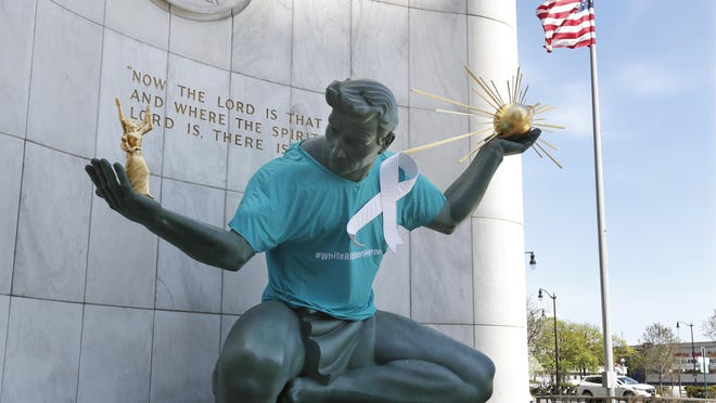 The Spirit of Detroit statue by Marshall Fredericks wears a white ribbon to honor essential workers, first responders and health care workers, Wednesday, May 6, 2020, in Detroit.